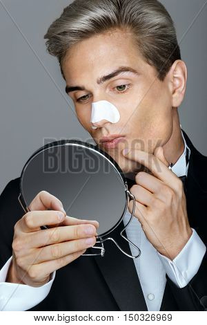 Man looking in the mirror pointing at his acne. Photo of elegant man applying clear-up strips on nose for remove blackheads. Beauty & Skin care concept.