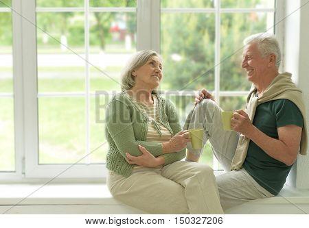 happy Senior couple drinking tea sitting on windowsill at home