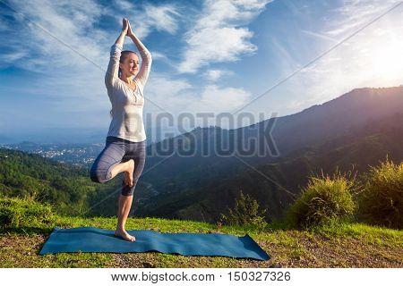 Yoga practice outdoors - woman practices balance yoga asana Vrikshasana tree pose in Himalayas mountains outdoors in the morning. Himachal Pradesh, India. Panorama