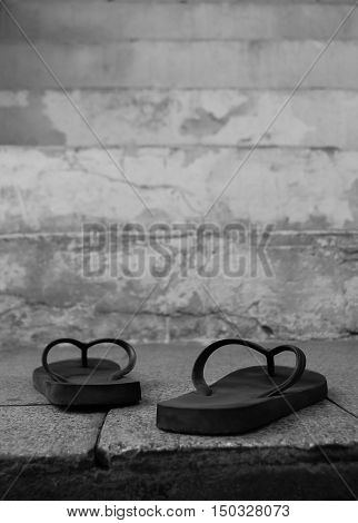 Black and white picture of strap sandals on a staircase