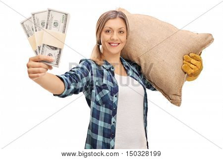 Female farmer holding stacks of money and carrying a sack isolated on white background