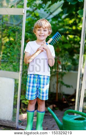 Smiling little kid boy watering plants and vegetables with can and working with garden hoe in greenhouse. Preschool child helping on sunny summer day. Family, garden, gardening, lifestyle