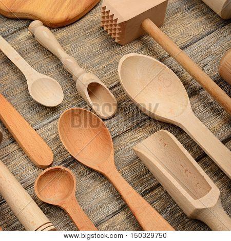 Set kitchen utensils on wooden table. Spoon, fork, rolling pin, hammer kitchen, kitchen spatula. Top view.