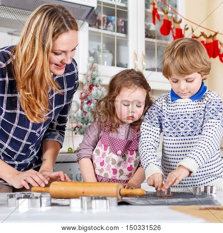 Happy family baking Christmas cookies at home. Little brother, sister and mother having fun in domestic decorated kitchen. Traditional leisure with kids on Xmas