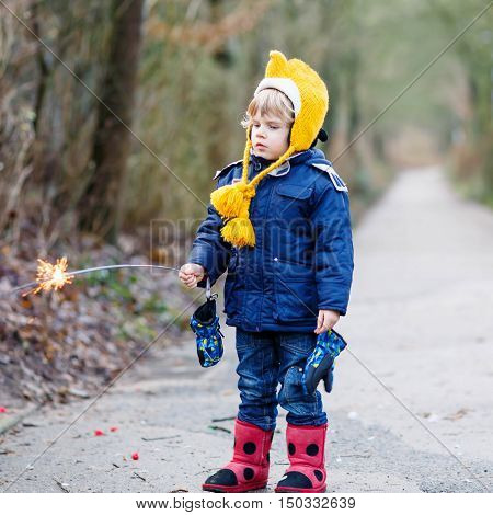 Two little kids, best friends in winter clothes holding burning sparkler on New Year's Eve. Safe fireworks for kids concept. Happy sibling  boys outdoors.
