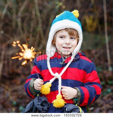 Funny little boy in winter clothes holding burning sparkler on New Year's Eve. Safe fireworks for kids concept. Happy kid playing outdoors.
