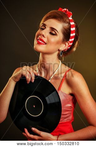 Girl in pin-up style keeps vinyl record. Pin-up retro female style. Girl adores to music.