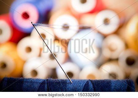 detail of a needle with thread in the workroomshallow depth of field