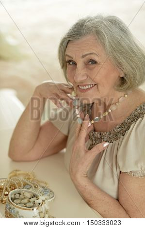 happy Senior woman portrait with beads at home