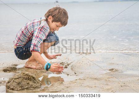 Happy child boy having fun on natural sea background