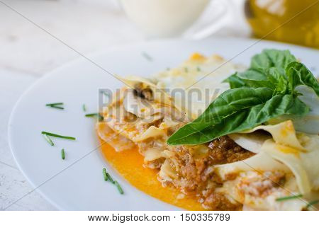 Close-up of a traditional lasagna made with minced beef bolognese sauce and bechamel sauce topped with basil. Portion of tasty homemade lasagna on wooden table. Italian food concept. Selective focus.