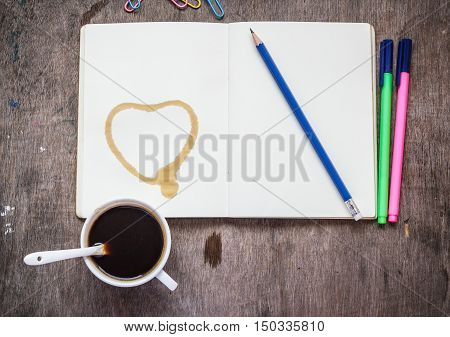 Notebook with pencil colored pens paperclip and coffee on wooden table background.