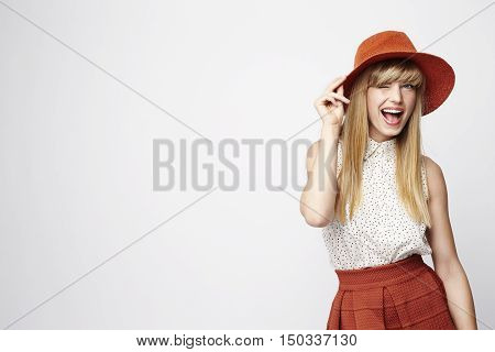 Blond woman with a wink wearing hat studio