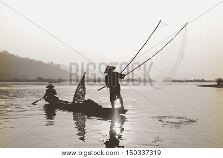 Silhouette of asia Fisherman net casting on the boat  on morning time sunrise