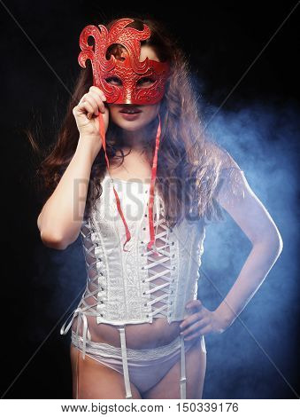 young sexy woman in white  lingerie wearing mask
