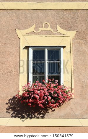 Renaissance window with a pot of pink flowers