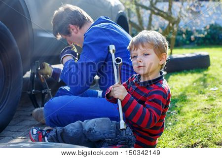 Happy blond kid boy and his father changing wheels on car with pneumatic wrench. Man in uniform teaching his son working with tools.