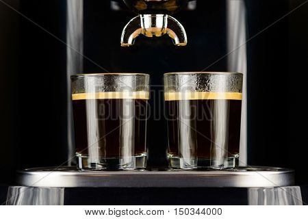 Two espresso coffees in glass cups on coffee machine