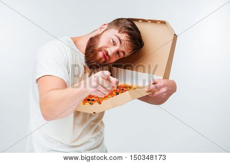 Funny bearded man holding pizza box and pointing at camera isolated on white background