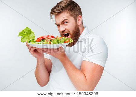 Young hungry bearded man eating salad isolated on white background