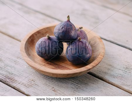 on a wooden table Wooden plate with ripe figs