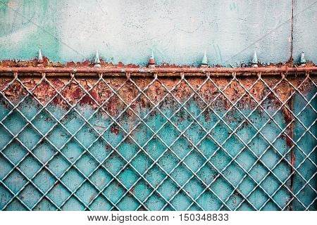 old metal rusty fence with notched on gray worn wall background