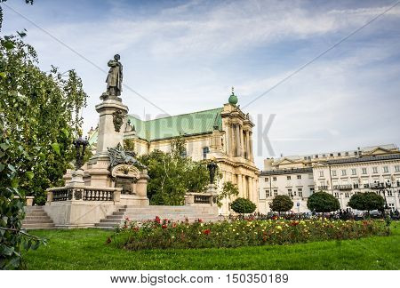 WARSAW POLAND - SEPTEMBER 27: Adam Mickiewicz Monument and Church of the Assumption of the Virgin Mary and of St. Joseph or Carmelite Church at Krakowskie Przedmiescie in Warsaw Poland on September 27 2016