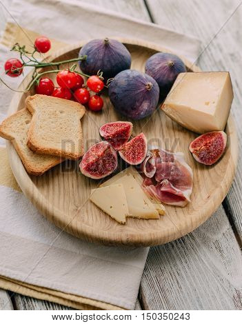 on a wooden table Wooden plate with ripe figs meat cheese and crackers