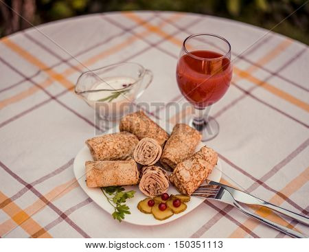 Tasty pancakes with meat on white plate closeup. Crepes stuffed with finely cut meat. glass of tomato juice and white sauce.