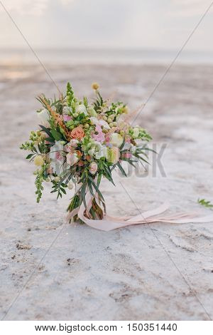 at sunset on the beach with salt crystals delicate bouquet of flowers