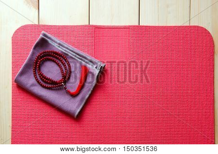 Accessories for yoga and meditation. Open mat and mala beads on wooden background with copyspace.