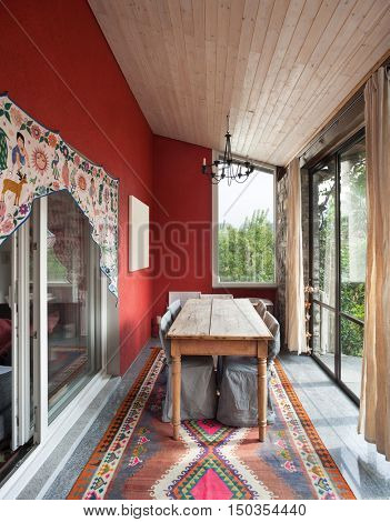 Interior, veranda with old dining table, carpet on the floor