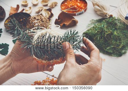 Creative diy craft hobby. Making handmade craft christmas ornaments, balls and garlands from spruce tree. Woman's leisure, holiday decorations. POV view of female hands at white wood background