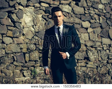 Man young handsome elegant model wears suit white shirt with black skinny necktie looks in camera poses outdoor on masonry background