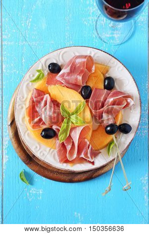 Parma ham with melon and glass of red wine