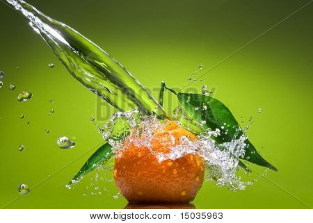 Tangerine with green leaves and water splash on green background