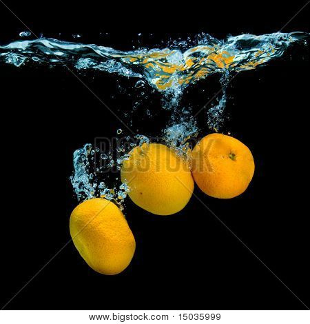 Fresh tangerines dropped into water with bubbles on black