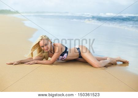 Beautiful woman with long legs in the blue bikini on the lonely beach in the rays of sun. Photo with shallow dept of field.