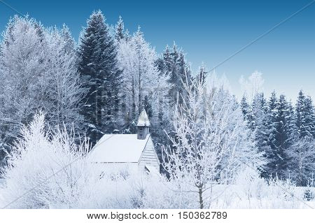 Snow-capped little wooden chapel in frosty winter forest. Tranquil beautiful view in Germany Bavaria province Allgaeu with deep blue sky.