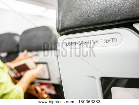 Close up fasten seat belt at backrest on airplane.