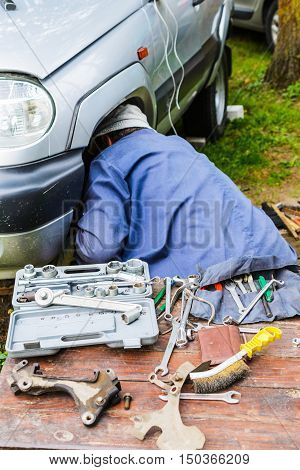 Man repairing the front suspension of the car in the field. On a wooden table scattered various tools.