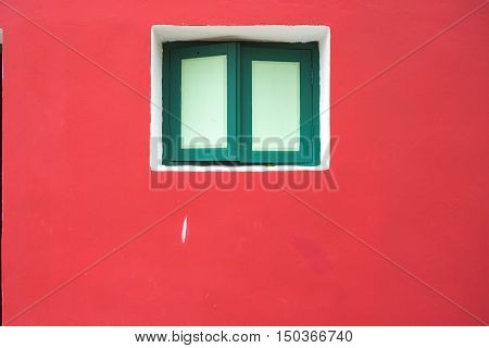 green wood window on a pink wall. Window with closed green window in the wall of the house.