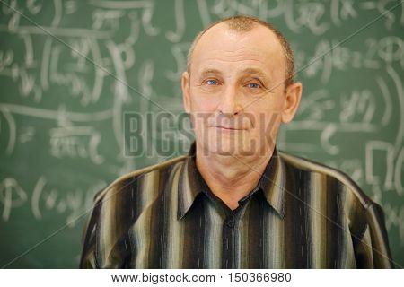 Old teacher stands near blackboard in classroom, shallow dof