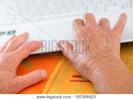 Closeup on pair of old hands typing on a laptop ontop of a desk.