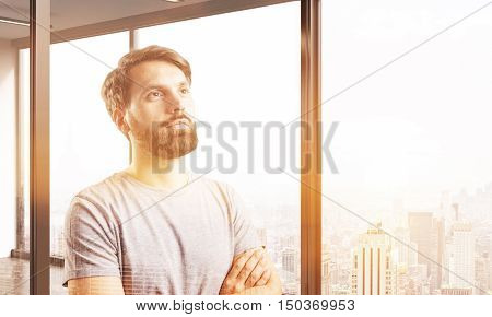Portrait of bearded man in T-shirt standing near panoramic window with sunlit cityscape and planning to conquer the world. Mock up. Toned image