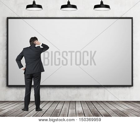 Rear view of man in suit staring at blank whiteboard in confusion. Classroom with concrete wall and wooden floor. Concept of creativity and lack of ideas.