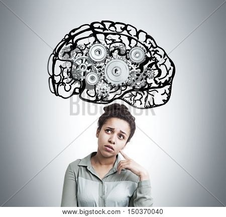 African American girl standing against light gray wall with brain sketch and gears on it. Concept of thought process