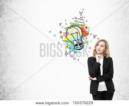 Portrait of red haired businesswoman standing near concrete wall with colorful light bubl sketch. Concept of bright idea. Mock up
