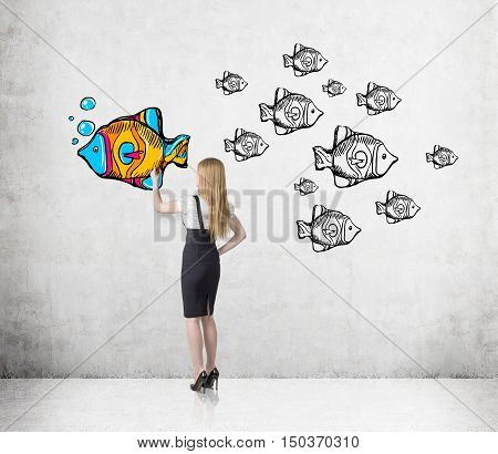 Rear view of woman with blond hair coloring a fish sketch on concrete wall. All fish are black and white. One is colored and swimming in different direction. Concept of original way of thought