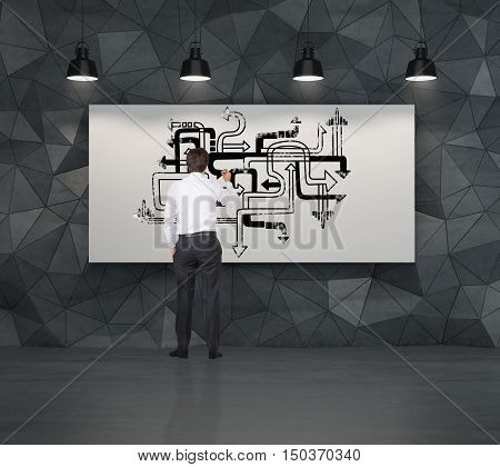 Rear view of businessman drawing arrow pipeline sketch on large poster in room with black walls. Concept of decision making